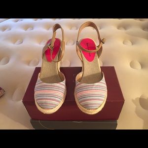 Multicolored straw wedge shoes with brown straps.